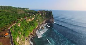 Uluwatu cliff aerial footage, Bali, Indonesia. Camera moves along the cliff. Aerial footage of Uluwatu cliff. Camera moves along the cliff to temple. Forest stock video