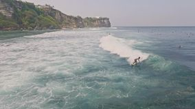 Uluwatu que practica surf la cámara lenta aérea de Bali almacen de metraje de vídeo