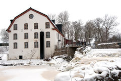 Ulva mill (Ulva kvarn) and the frozen waterfall. The mill at Ulva village with its frozen waterfall in Uppland, Sweden royalty free stock image