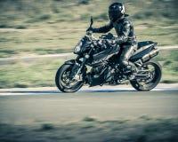 Ulyanovsk, Rússia - 19 de agosto de 2017 Um piloto da motocicleta em uma motocicleta clássica preta treina em uma trilha dos espo Fotos de Stock Royalty Free