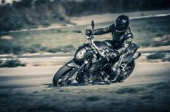Ulyanovsk, Rússia - 19 de agosto de 2017 Um piloto da motocicleta em uma motocicleta clássica preta treina em uma trilha dos espo Fotos de Stock