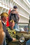 ULYANOVSK, RÚSSIA - 9 DE MAIO DE 2016: Homens sob a forma da era soviética da guerra mundial 2 do exército com o carro velho Foto de Stock Royalty Free