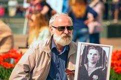 ULYANOVSK, RÚSSIA - 9 DE MAIO DE 2016: Um homem idoso com um retrato da relativo ao regimento imortal Imagens de Stock Royalty Free