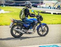 Ulyanovsk, Rusia - 10 de junio de 2017 Muchacha en una raza negra de la chaqueta en una motocicleta azul en una pista de los depo Imágenes de archivo libres de regalías