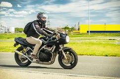 Ulyanovsk, Rusia - 10 de junio de 2017 Un corredor de la motocicleta en un casco negro con una mochila entrena en una motocicleta Imagen de archivo libre de regalías