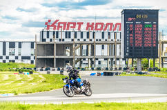 Ulyanovsk, Russia - June 10, 2017. Girl in a black fnd pink jacket with a backpack trains race on a blue motorcycle on a. Cartholl sports track stock photo