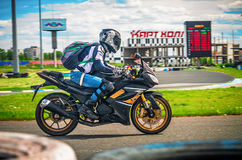 Ulyanovsk, Russia - June 10, 2017. A motorcycle racer with a backpack trains on a motorcycle on a sports track. Motion Stock Photo
