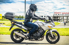 Ulyanovsk, Russia - June 10, 2017. A motorcycle racer in a black helmet with a backpack trains on a motorcycle with road Royalty Free Stock Photo