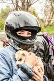 Ulyanovsk, Russia - May 03 2019: Opening of the motorcycle season. Girl in a motorcycle helmet with a husky puppy in her. Arms stock photography