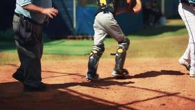 Um árbitro, um coletor e uma massa no meio de um jogo durante o jogo de basebol video estoque