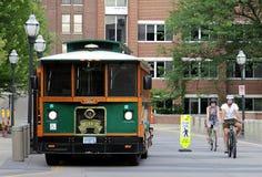 Um ônibus e dois ciclistas na universidade de Minnesota fotos de stock royalty free