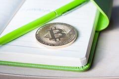 Um único bitcoin dourado em um bloco de notas verde foto de stock