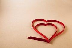 Um único coração vermelho da fita em um fundo bege morno claro Foto de Stock Royalty Free