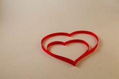 Um único coração vermelho da fita em um fundo bege morno claro Fotografia de Stock Royalty Free