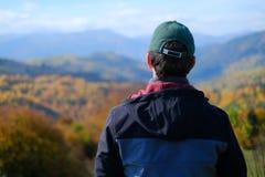Um único homem no revestimento cinzento que está no monte e na observação da montanha Imagem de Stock