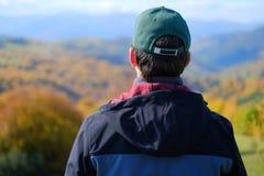 Um único homem no revestimento cinzento que está no monte e na observação da montanha Fotografia de Stock Royalty Free