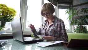Um único pensionista da mulher trabalha com seu computador vídeos de arquivo
