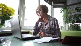 Um único pensionista superior da mulher trabalha com seu computador video estoque