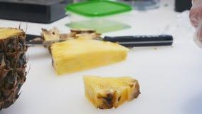 Um abacaxi do corte da pessoa na cozinha filme