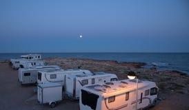 Um acampamento de carros da caravana estacionou no beira-mar do mar Mediterrâneo na noite nova Crepúsculo e luar agradáveis imagens de stock royalty free