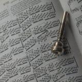 Um adaptador bucal de prata velho da trombeta no livro de partitura Foto de Stock