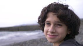 Um adolescente bonito com cabelo encaracolado contra o contexto do mar 4k, movimento lento filme