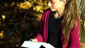 Um adolescente bonito novo senta-se sob uma árvore na floresta do outono e lê-se um livro Sonha A menina é sereno e filme