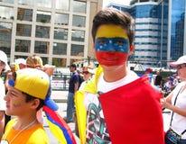Um adolescente com a bandeira venezuelana pintada em sua cara foto de stock