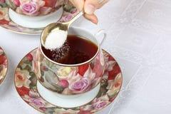 Um adolescente derrama uma colher de açúcar no chá preto imagem de stock