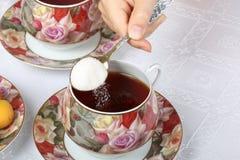 Um adolescente derrama uma colher de açúcar no chá preto fotos de stock royalty free
