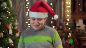 Um adolescente do menino em um chapéu Santa Claus está dançando perto da árvore de Natal Feriado do Natal, ano novo feliz video estoque