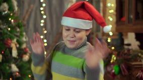 Um adolescente do menino em um chapéu Santa Claus está dançando perto da árvore de Natal Feriado do Natal, ano novo feliz filme