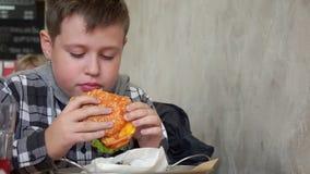 Um adolescente em um café que come um Hamburger Está com fome, slowmotion vídeos de arquivo