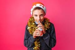 Um adolescente em um chapéu de Santa e em um ouropel em seu pescoço, suco bebendo fotografia de stock royalty free