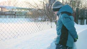 Um adolescente em um parque do inverno pinta um sincelo na neve Dia ensolarado gelado nevado Divertimento e jogos no ar fresco filme