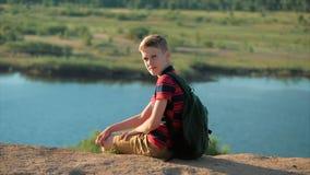 Um adolescente em uma camisa vermelha com uma trouxa atrás dele, no por do sol, sentando-se em um monte alto apreciando a naturez video estoque