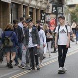 Um adolescente está montando um skate seus amigos são próximos Fotos de Stock Royalty Free