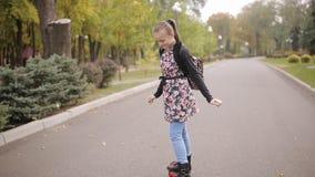 Um adolescente está montando um 'trotinette' eletrônico a menina dança no giroscópio vídeos de arquivo