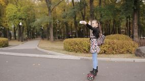 Um adolescente está montando um 'trotinette' eletrônico a menina dança no giroscópio video estoque
