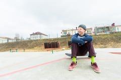 Um adolescente está sentando-se em um skate no parque e no sorriso O conceito do passatempo do tempo livre para adolescentes no Fotografia de Stock Royalty Free