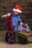 Um adolescente europeu típico em um chapéu de Santa Claus olha em uma caixa de madeira aberta e retira decorações do Natal dela fotos de stock