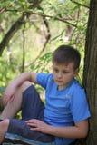 Um adolescente levanta para um fotógrafo ao andar no parque Senta-se, inclinando-se em uma árvore imagens de stock royalty free