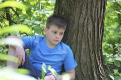 Um adolescente levanta para um fotógrafo ao andar no parque Senta-se, inclinando-se em uma árvore fotos de stock royalty free