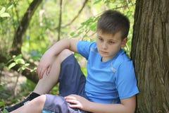 Um adolescente levanta para um fotógrafo ao andar no parque Senta-se, inclinando-se em uma árvore imagem de stock