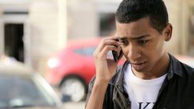 Um adolescente muito novo está falando seriamente através do telefone celular video estoque