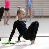 Um adolescente novo prepara-se para o desempenho, aquecendo-se e executa-se elementos ginásticos nas competições Fotografia de Stock Royalty Free