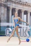 Um adolescente novo prepara-se para o desempenho, aquecendo-se e executa-se elementos ginásticos nas competições Imagem de Stock