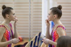 Um adolescente novo prepara-se para o desempenho, aquecendo-se e executa-se elementos ginásticos nas competições Fotos de Stock Royalty Free