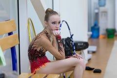 Um adolescente novo prepara-se para o desempenho, aquecendo-se e executa-se elementos ginásticos nas competições Fotos de Stock