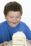 Um adolescente obeso que olha o bolo Fotos de Stock